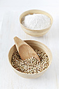 Bowl of buckwheat grains with wooden shovel and bowl of buckwheat flour on white wooden table - EVGF000432