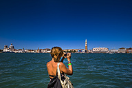 Italy, Venice, Woman taking picture of city - EJW000248