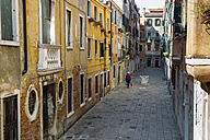 Italy, Venice, Woman walking in alley - EJW000253