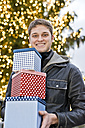 Young man holding three gift boxes in front of lighted Christmas tree - CLPF000068