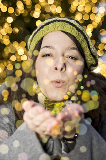Portrait of young woman blowing golden glitter - CLPF000065