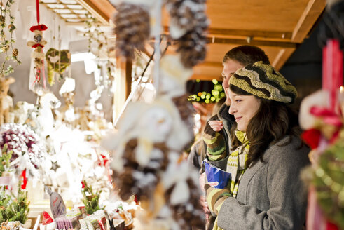 Germany, Berlin, young couple watching offerings at Christmas market - CLPF000060