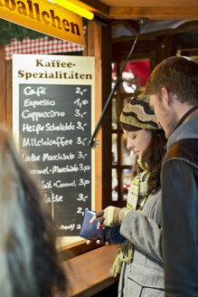 Germany, Berlin, young couple at Christmas market - CLPF000058