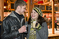 Germany, Berlin, happy young couple with hot beverages at Christmas market - CLPF000054
