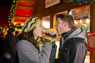 Germany, Berlin, young couple eating grill sausage at Christmas market - CLPF000048
