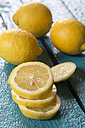 Whole and sliced lemons on blue wooden table - SARF000247