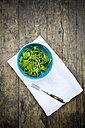 Bowl of winter purslane salad (Claytonia perfoliata) on white cloth napkin and wooden table, view from above - LVF000670