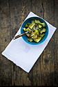 Bowl of avocado salad (Persea americana) on white cloth napkin and wooden table - LVF000666