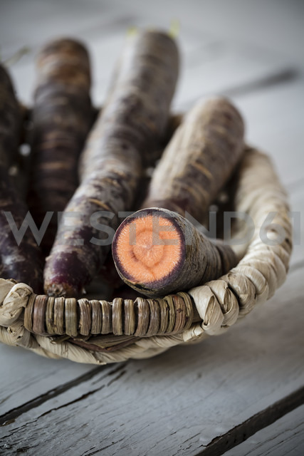 Basket of Purple Haze carrots on grey wooden table, close-up - SARF000243