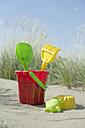Colourful sandbox toys on sandy beach - CRF002570