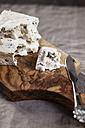 Pieces of gorgonzola cheese on chopping board - SBDF000605