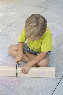 Little boy sawing wooden bar - CRF002578