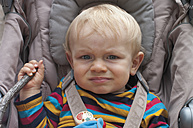 Portrait of unhappy toddler sitting in buggy - MU001419