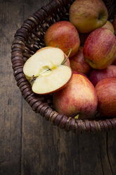 Basket of sliced and whole red apples on wooden table - LVF000684