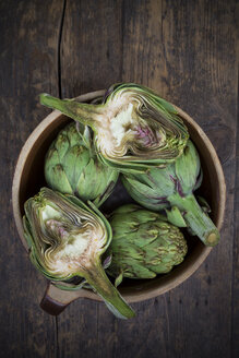Bowl of organic artichokes on wooden table, view from above - LVF000679