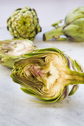 Sliced and whole organic artichokes on white marble - LVF000678