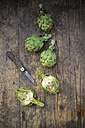 Sliced and whole organic artichokes and kitchen knife on wooden table, view from above - LVF000676