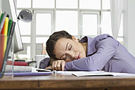 Woman at home sleeping at desk with computer - RBYF000336