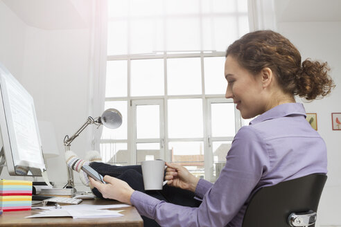 Woman at desk having a coffee break - RBYF000340