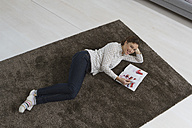 Woman lying on carpet reading magazine - RBYF000349