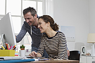 Man and woman at home sitting at desk with computer - RBYF000474