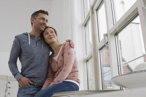 Smiling couple embracing at the window - RBYF000378