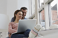 Couple sitting on windowsill using laptop - RBYF000381