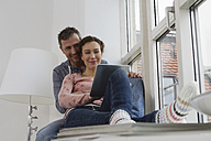 Couple sitting on windowsill using tablet computer - RBYF000479