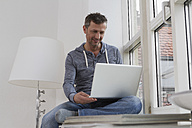 Man sitting on windowsill using laptop - RBYF000387