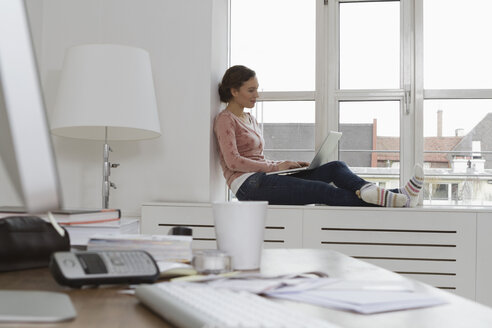 Woman sitting on windowsill using laptop - RBYF000418