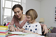 Mother with daughter at desk - RBYF000397