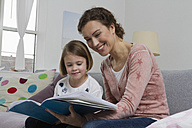 Mother and daughter on couch with book - RBYF000409