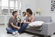 Mother, father and daughter at home on couch - RBYF000412