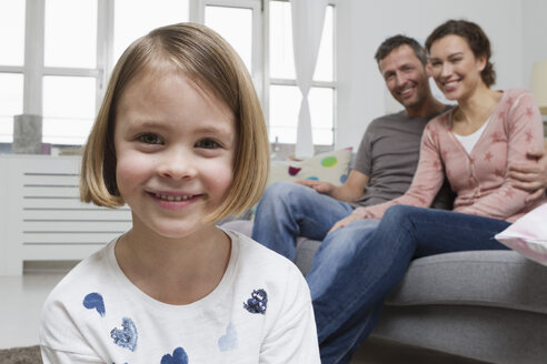 Blond girl in living room with parents in background - RBYF000415