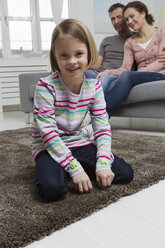 Blond girl in living room with parents in background - RBYF000424