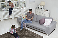 Mother, father and daughter using portable devices in living room - RBYF000482