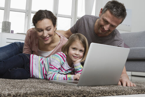 Father, mother and daughter using laptop on carpet in living room - RBYF000465