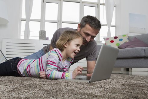 Father and daughter using laptop on carpet in living room - RBYF000486
