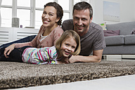 Happy mother, father and daughter lying on carpet in living room - RBYF000489