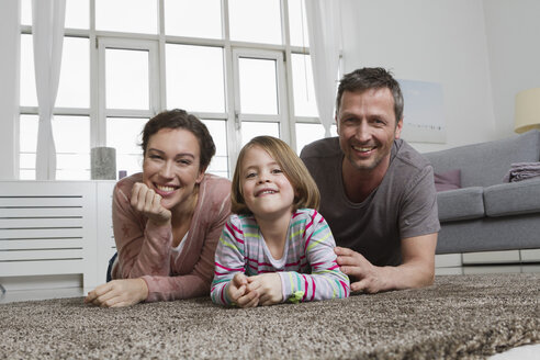 Happy mother, father and daughter lying on carpet in living room - RBYF000492