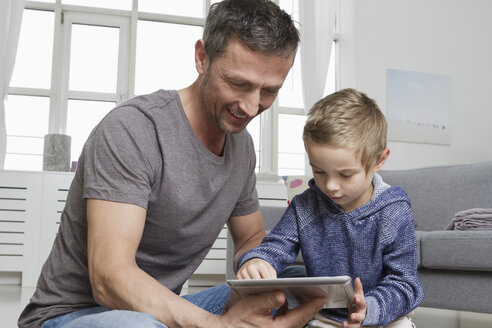 Father and son using tablet computer in living room - RBYF000495