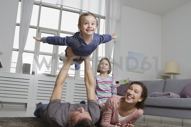 Playful family in living room - RBYF000500