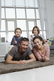 Happy family of four in living room - RBYF000426