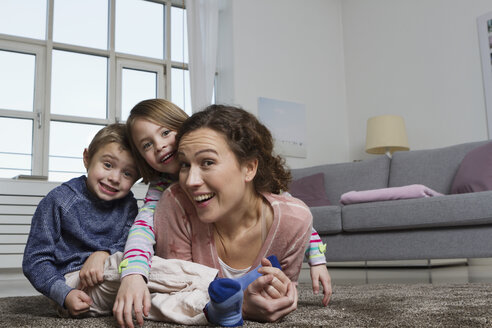 Happy mother, son and daughter lying on carpet in living room - RBYF000429