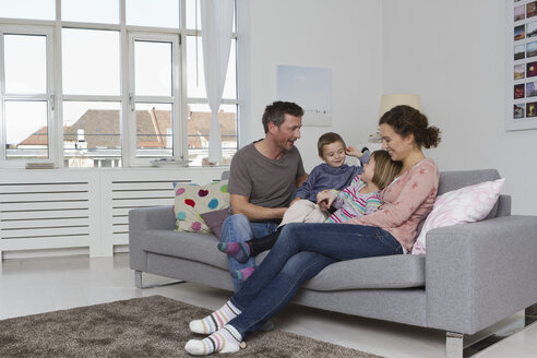 Happy family of four sitting on couch - RBYF000432