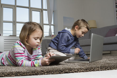 Brother and sister using laptop and tablet computer on carpet in living room - RBYF000435