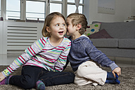 Brother and sister whispering on carpet in living room - RBYF000438