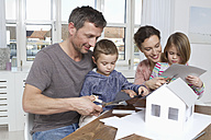 Family of four constructing house model - RBYF000452