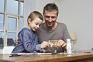 Father and son tinkering model airplane - RBYF000460