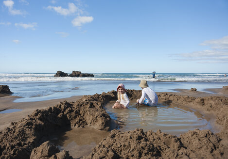 New Zealand, North Island, Waikato, Coromandel Peninsula, Hot Water Beach, kids playing in thermal pools - JB000025